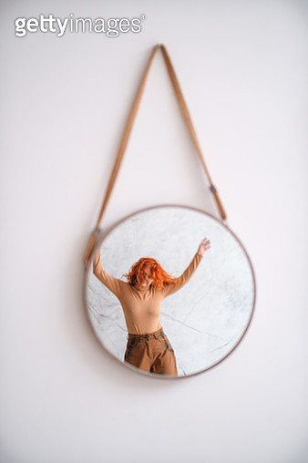 Reflection Of Woman In Mirror Hanging On Wall - gettyimageskorea