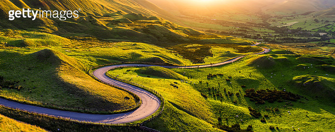 Summer evening light with the famous twisty road that runs down the South side of the valley towards Edale village. Taken from the slopes of Mam Tor near Castleton, Buxton.   Peak District National park. England. UK. - gettyimageskorea
