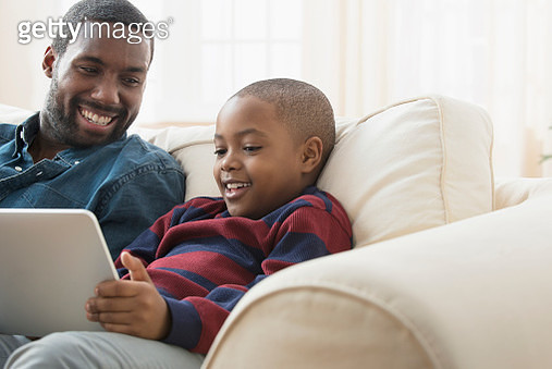 Father and son using digital tablet on sofa - gettyimageskorea