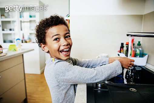 Young Boy Grinning While Washing Hands In Kitchen Sink - gettyimageskorea