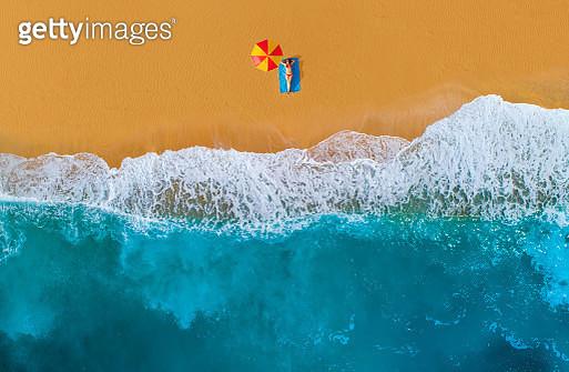 Woman sunbathing at sandy beach. Mediterranean sea. - gettyimageskorea