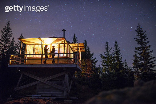 Low angle view of women standing in illuminated cottage at night - gettyimageskorea