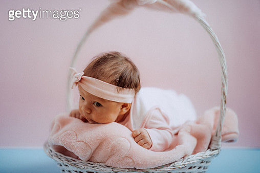 Newborn baby girl in white knitted basket - gettyimageskorea