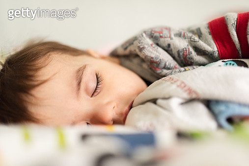 Close Up Portrait of Toddler Sleeping on a Bed Attempting to Recover from the Cold and Flu Season. - gettyimageskorea