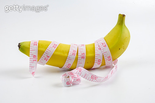 Close-Up Of Tape Measure Rolled On Banana Against White Background - gettyimageskorea