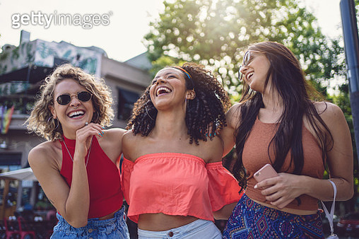 Cheerful friends, three Hispanic women. enjoying a sunny day outdoors in the city. - gettyimageskorea