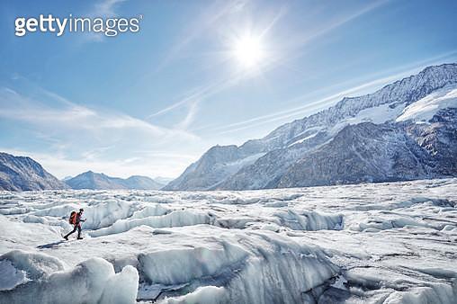 Hiker on glacier with distant mountains, Aletsch Glacier, Switzerland - gettyimageskorea
