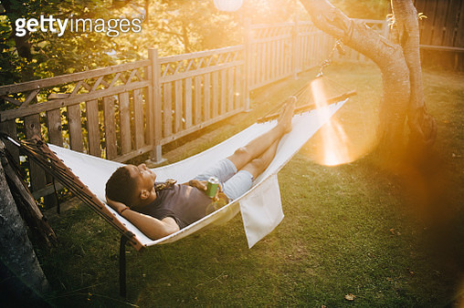 High angle view of young man with drink lying on hammock in back yard - gettyimageskorea