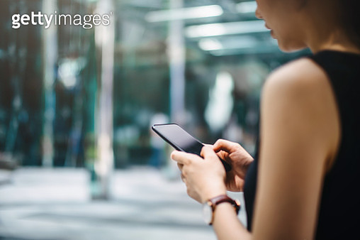 Close up of busy businesswoman emailing on mobile phone by office towers in downtown financial district - gettyimageskorea