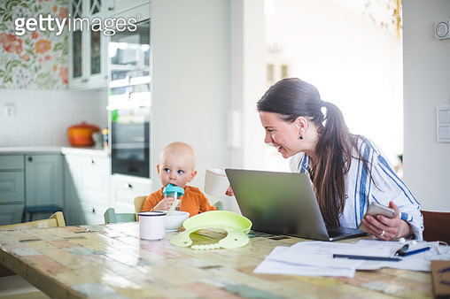 Smiling working mother talking with daughter while freelancing at dining table in kitchen - gettyimageskorea