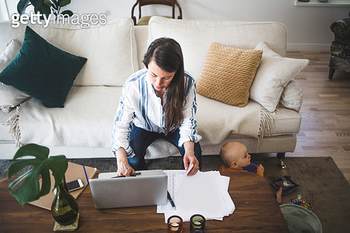 High angle view of female entrepreneur concentrating on work while daughter playing at home office - gettyimageskorea
