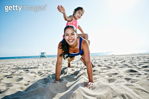 Mother doing push-ups with daughter at beach - gettyimageskorea
