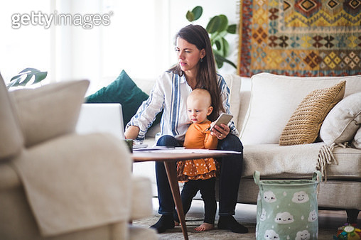 Multi-tasking mother using laptop while taking care of daughter in living room - gettyimageskorea