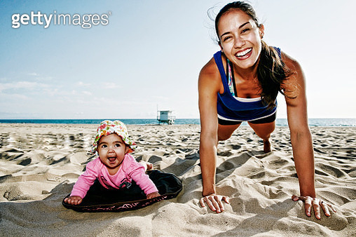 Mother and daughter doing push-ups at beach - gettyimageskorea