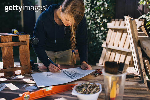 Blondhaired woman drawing a design sketch outdoor. - gettyimageskorea