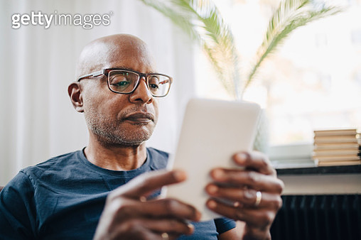 Retired senior man reading e-book in room at home - gettyimageskorea