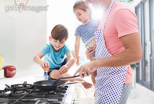 Father cooking breakfast at stove with daughter and son - gettyimageskorea