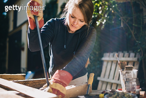 Blondhaired woman treating a europallet for upcycling later. - gettyimageskorea
