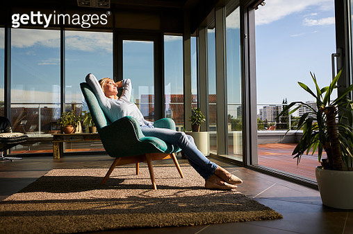 Mature woman relaxing in armchair in sunlight at home - gettyimageskorea