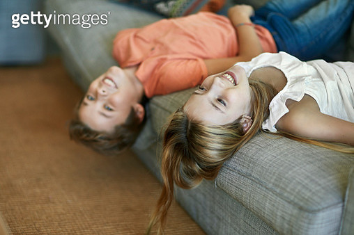 Close-up of playful young Spanish boy and girl lying upside down on family sofa and laughing while looking at camera. - gettyimageskorea