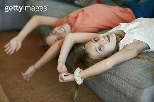 Close-up of Spanish pre-teen boy and girl lying upside down on sofa with arms over head and smiling at camera. - gettyimageskorea
