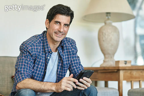 Close-up of casually dressed Spanish man in early 40s looking at camera while checking smart phone on sofa in family home. - gettyimageskorea