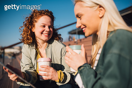 Girl friends smiling and talking - gettyimageskorea
