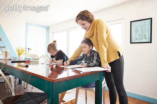 Mother homeschooling daughter and son at dining table - gettyimageskorea
