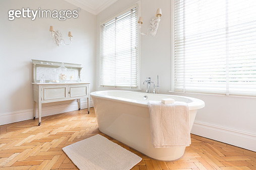 White, luxury home showcase interior bathroom with soaking tub and parquet hardwood floor - gettyimageskorea