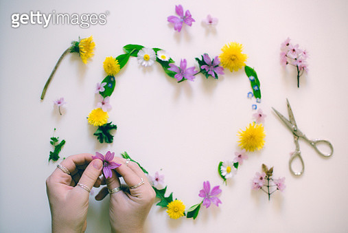 Woman's hands arranging spring flowers on white table - gettyimageskorea