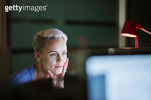 Serious businesswoman working late at computer in office - gettyimageskorea