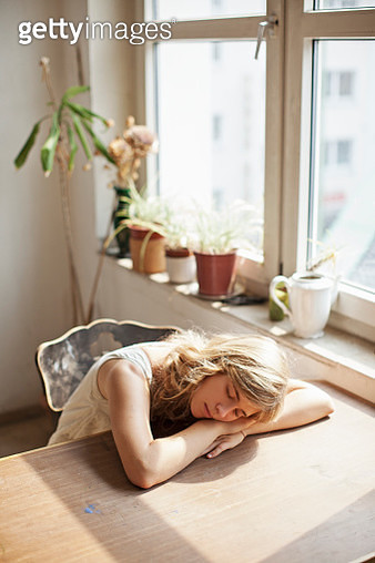 View of young adult woman sleeping at table - gettyimageskorea