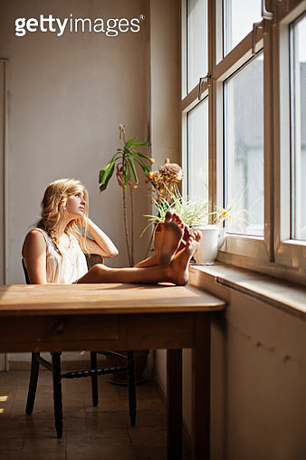 View of young adult woman looking through window - gettyimageskorea