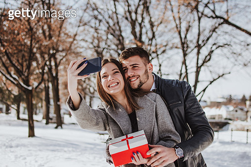 Cheerful young woman receiving a gift from her boyfriend - gettyimageskorea