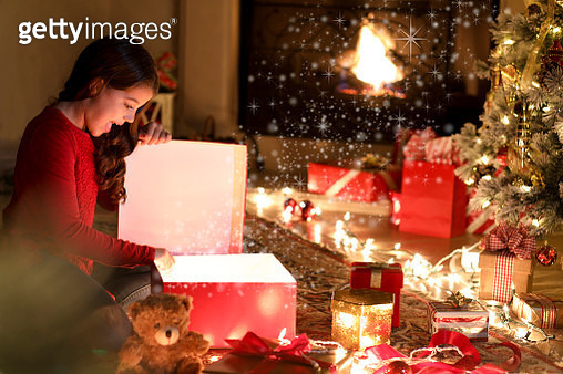 Little girl excitedly opens presents during Christmas season near tree. - gettyimageskorea