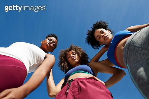 Directly below portrait of confident female friends in sportswear standing against blue sky on sunny day - gettyimageskorea