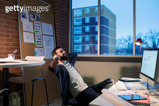 Graphic designer working late at computer in office - gettyimageskorea