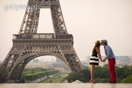 Couple kissing at the Eiffel Tower in Paris - gettyimageskorea
