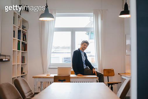 Portrait of smiling man sitting on table with laptop - gettyimageskorea