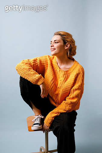 Smiling young woman sitting on chair in front of blue background wearing yellow knit pullover - gettyimageskorea