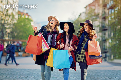 Girlfriends are walking on the street after shopping - gettyimageskorea