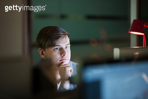 Serious businessman working late at computer in office - gettyimageskorea