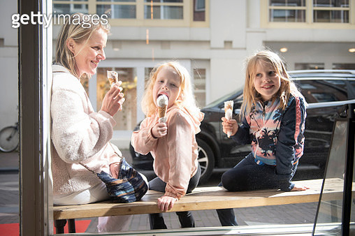 Mother and her two daughters sitting on a bench in front of an ice-cream shop, all looking in different directions, one looking at camera. - gettyimageskorea
