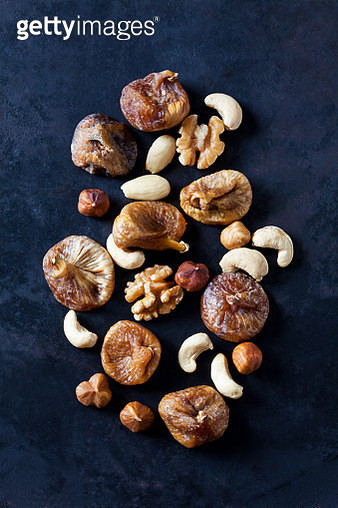 Dried figs, almonds and various nuts on dark ground - gettyimageskorea