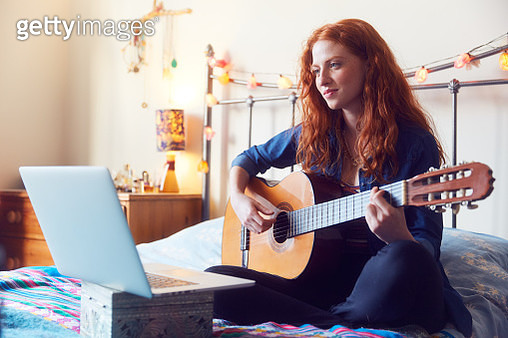Young woman on bed with guitar and laptop - gettyimageskorea