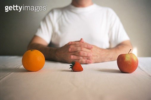 Midsection Of Man Having Fruits At Table - gettyimageskorea