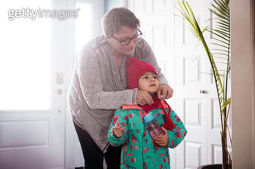 Grandma getting dressed her granddaughter to go to gymnastics in the lobby. It is winter so she put boots and winter coat and wool hat.  Photo was taken in Quebec Canada. - gettyimageskorea