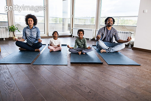 African American family meditating in Lotus position in the apartment. - gettyimageskorea