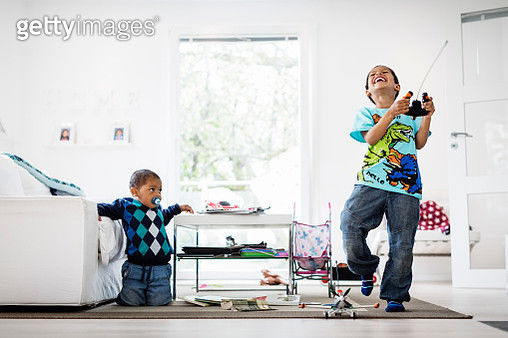 Boy looking at happy brother holding remote of model airplane at home - gettyimageskorea