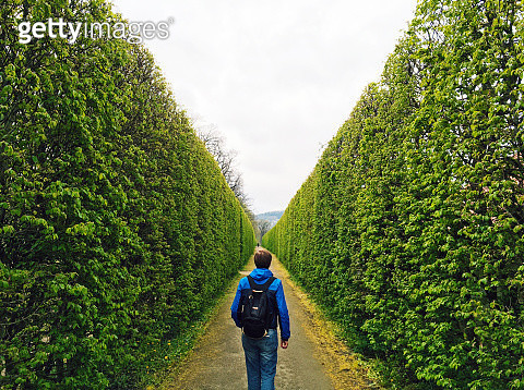 Man with backpack walking forward in a green tunnel - gettyimageskorea